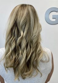 Ash blond hair painted balayage on long curls